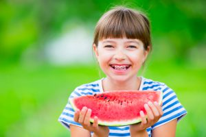 Child eating watermelon. Kids eat fruits in the garden. Pre teen girl in the garden holding a slice of water melon. happy girl kid eating watermelon. Girl kid with gasses and teeth braces